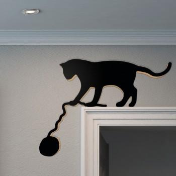 Schwarze Katze mit Wollknäuel auf Türrahmen